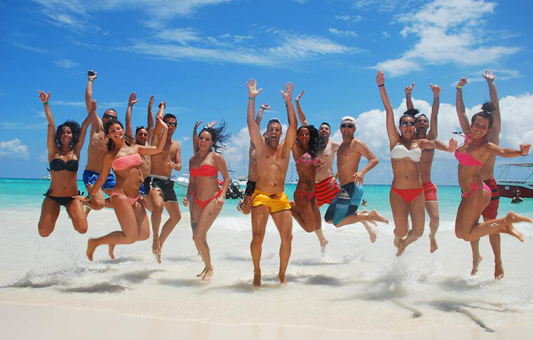 Group of people jumping in the air with hands up and the water lapping at their feet