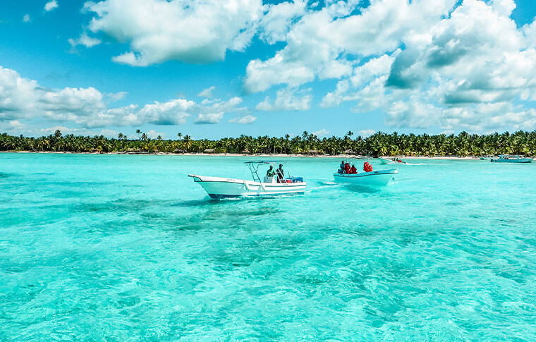 2 boats sailing close to the palm tree shore on crystal clear waters