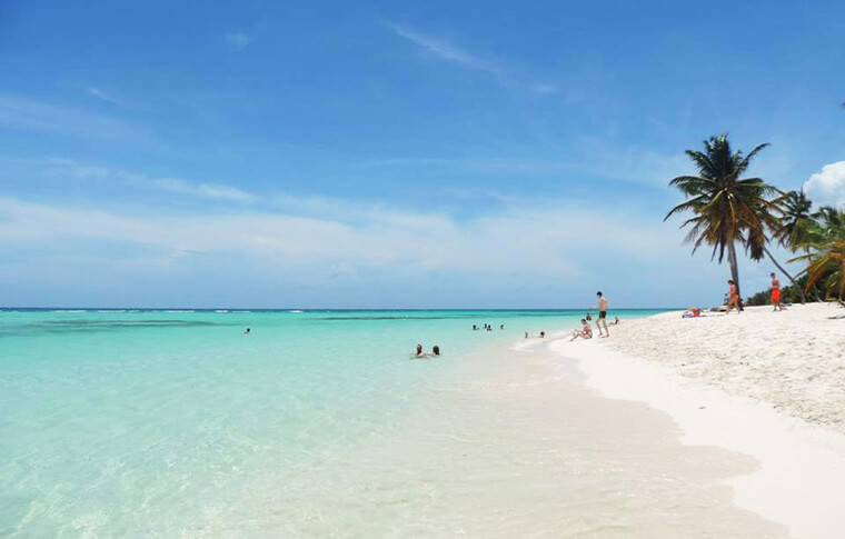 A stretching white sand beach with people swimming in the turquoise ocean