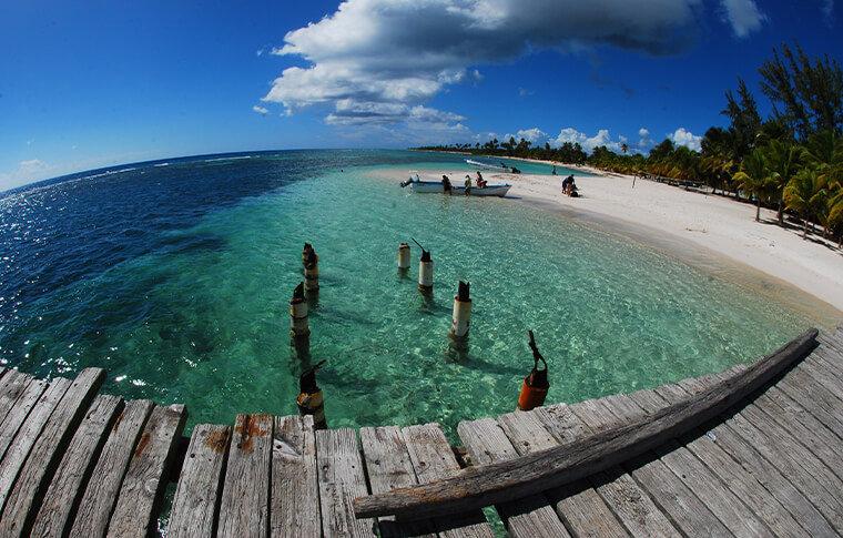 Photo from a wooden pier overlooking the clear ocean and white sands