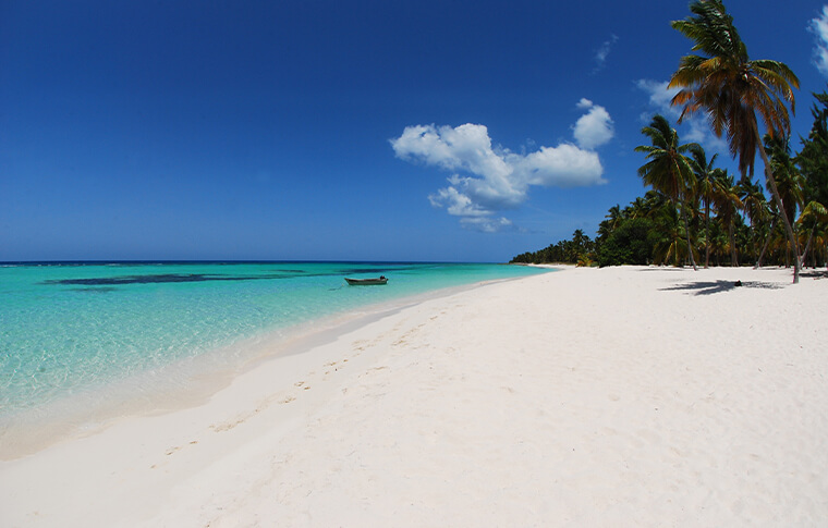 A stretching white sand beach with the turquoise water lapping on the shore