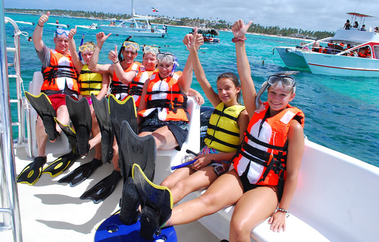 Group of snorkelers with lifejackets waving at the camera