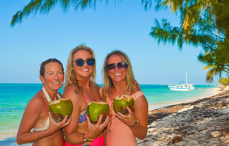 Three smiling ladies on an island holding a fresh coconut