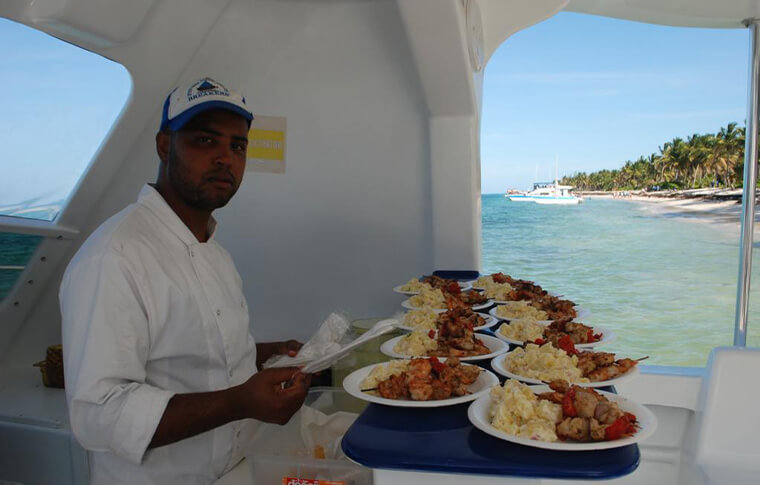 Person preparing plates of food on a boat