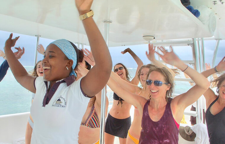 Staff member on the boat teaching a boat load of smiling people how to dance