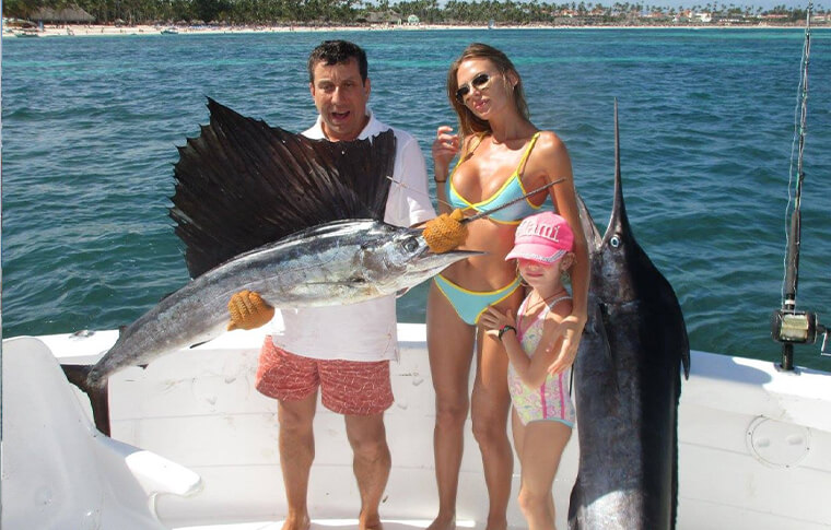2 people with small child holding a large fish on a boat