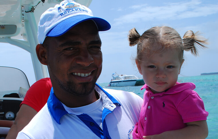 Breakers staff member holding small child on a boat posing for a picture