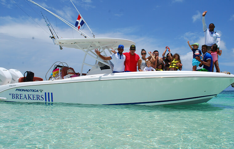 Group of people on a white boat floating on the clear waters