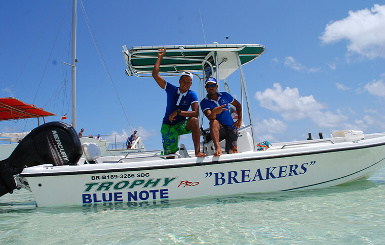 2 Breakers staff members with one leg up on the side of the boat posing for photo