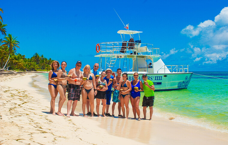 Group of people standing for a photo on the sandy beach infront of the boat in the water