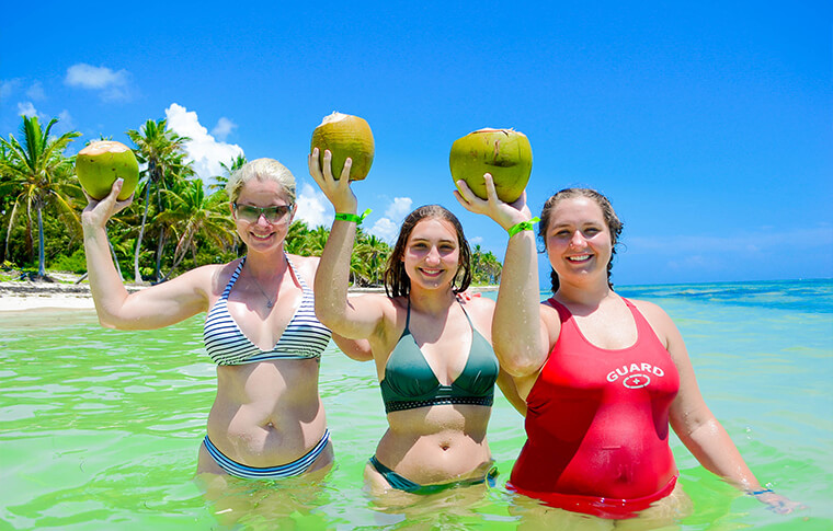 3 smiling ladies in wasit deep light green water holding fresh coconuts