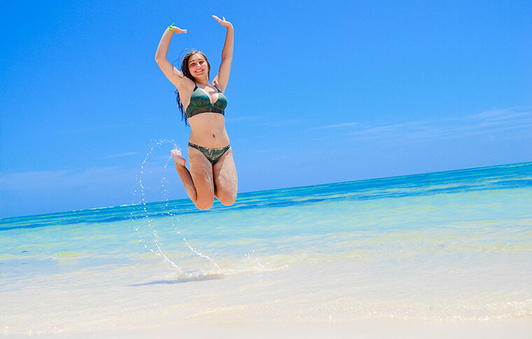 Lady in bikini jumping on the shore with hands in the air