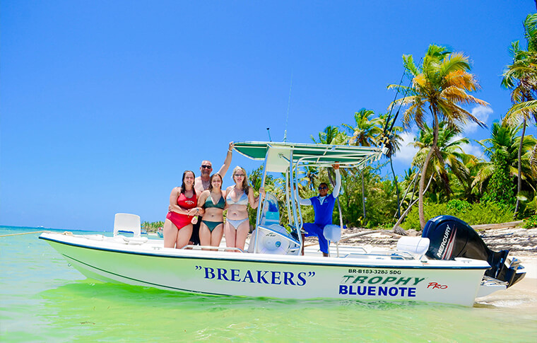 Breakers boat on crystal clear waters near the palm studded shore