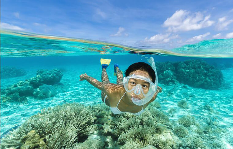 Smiling woman with snorkel on swimming above reef with photo taken underwater