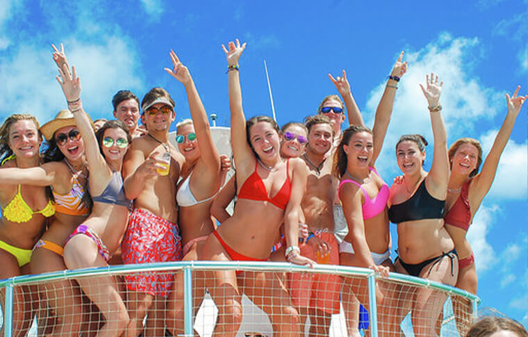 Big group of people standing at the end of a boat posing for a photo with hands in the air