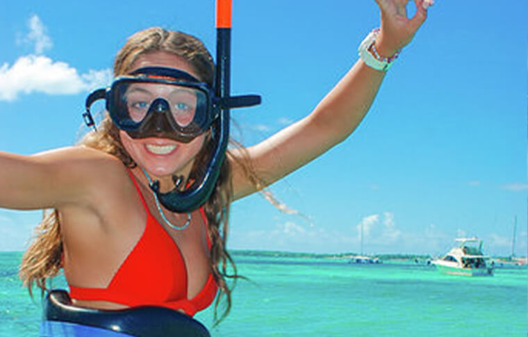 Lady in waist deep tropical waters with snorkel on posing for photo